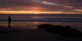 Photo of person on beach at sunset